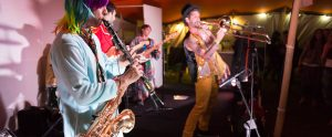 backyard rhythm orchestra on the green dragon solar stage brightly dressed clarinet and trumpet player