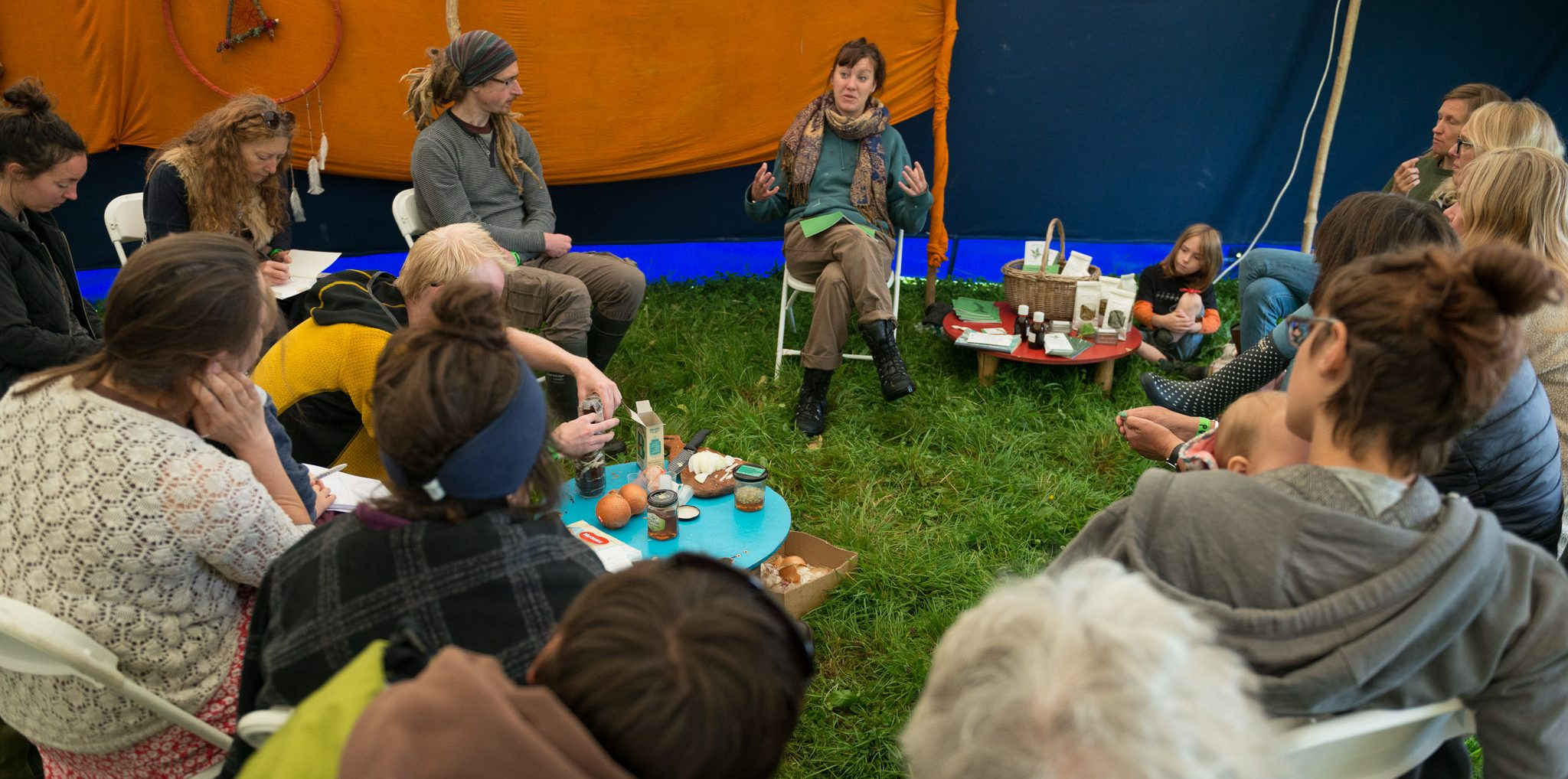 zoe nettles giving her kitchen medicines workshop to an interested group of 20 people sat in a large tent