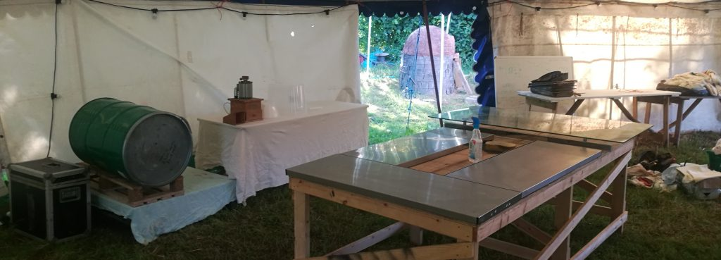 catering surfaces, grain mill, flour storage barrel in a marquee.