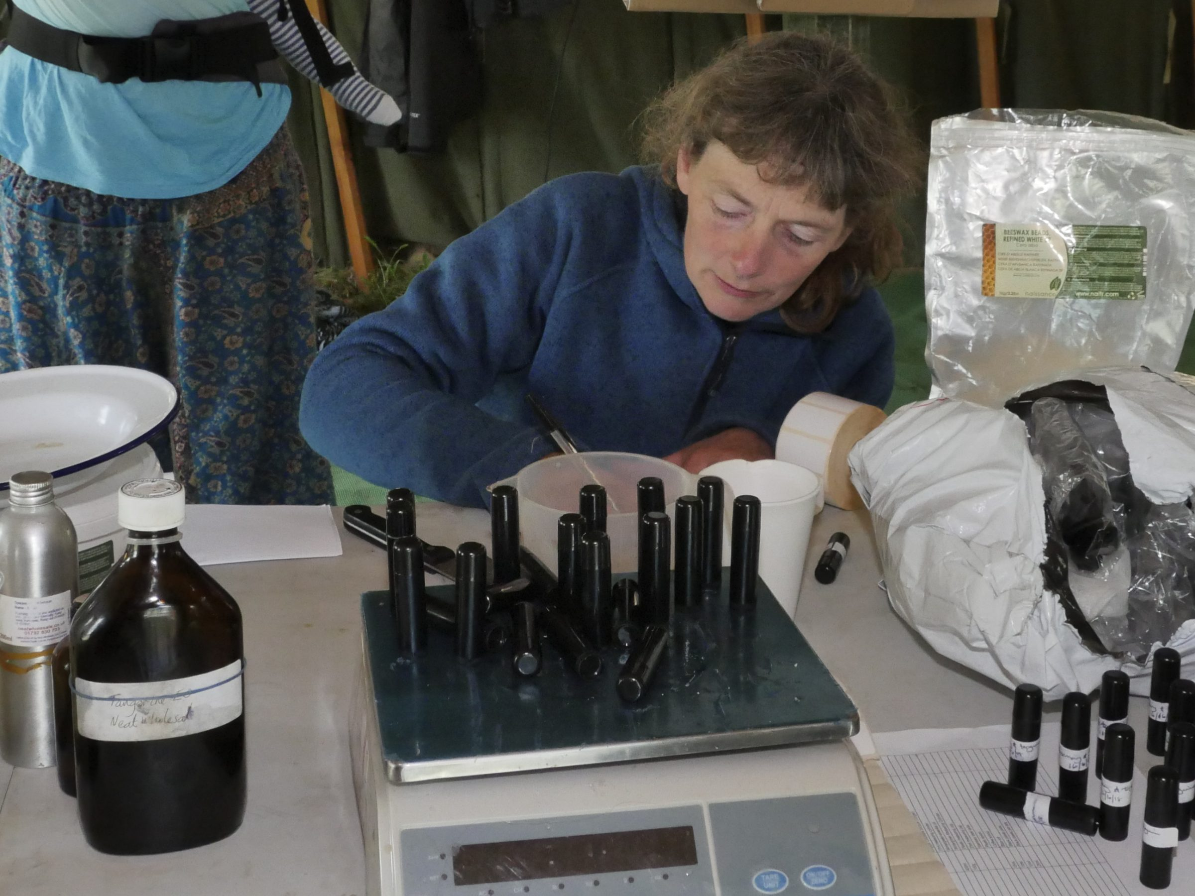 iain stewarts workshop a woman labels and weighs small bottles