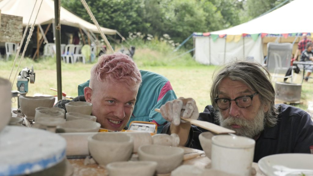 two people engrossed in making raku pottery with lots of finished pots ready to glaze