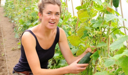 Rosalind in a polytunnel with green plants and produce